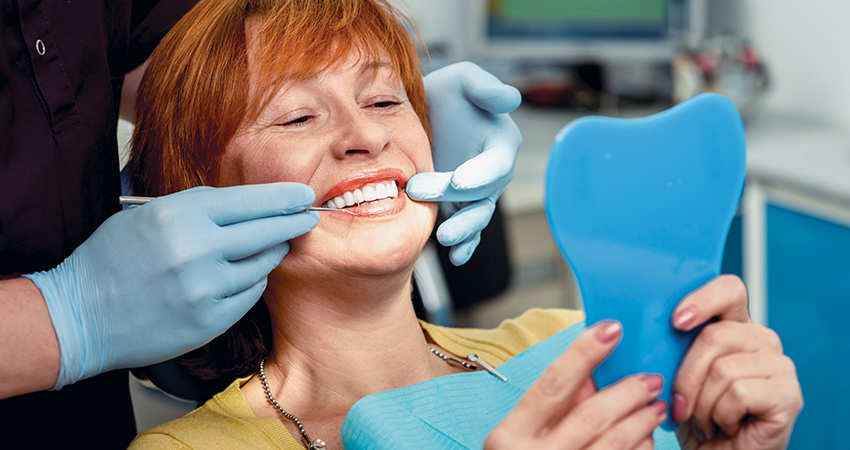 middle-aged woman admires beautiful new smile while in chair at dentist's office