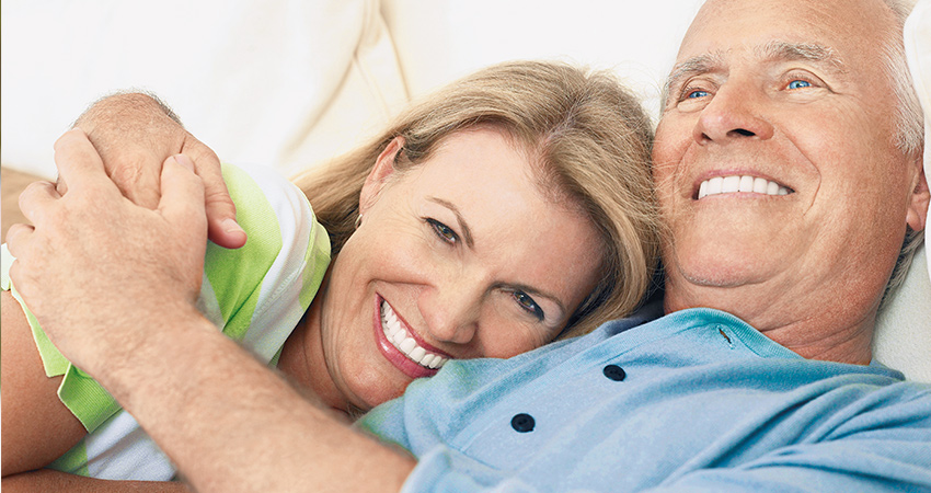 Retired couple lie down in bed and smile with their new dental implants in Waterloo