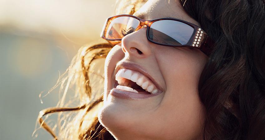 Closeup of caucasian woman with sunglasses with sun illuminating teeth