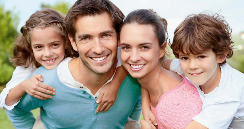 Caucasian family daughter father mother son heads together smiling